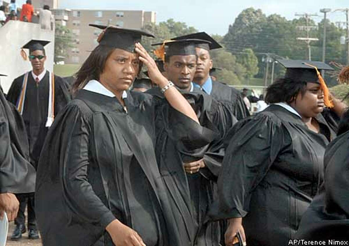 LaTosha tries to keep her cap in place while marching into Jack Sphinks stadium on the campus of Alcorn State University in Mississippi for commencement excercises where she recieved her degree in Accounting May 10, 2003 in Lorman, MS (AP Photo/ Terence Nimox)