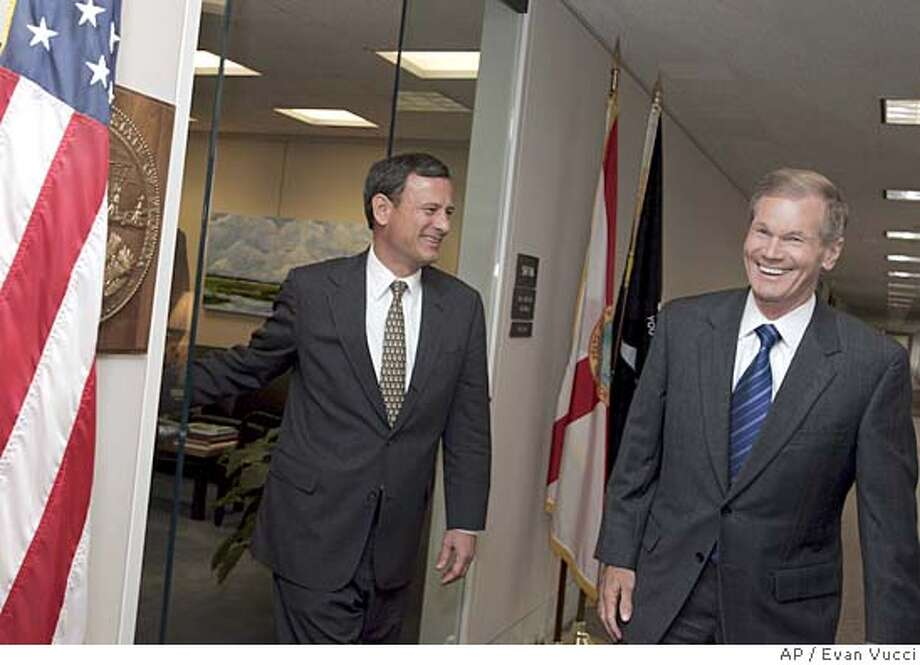 U.S. Supreme Court nominee Judge John Roberts, left, walks out of the office of Sen. Bill Nelson, D-Fla., right, after a meeting on Wednesday, Aug. 10, 2005, in Washington. (AP Photo/Evan Vucci) Photo: EVAN VUCCI