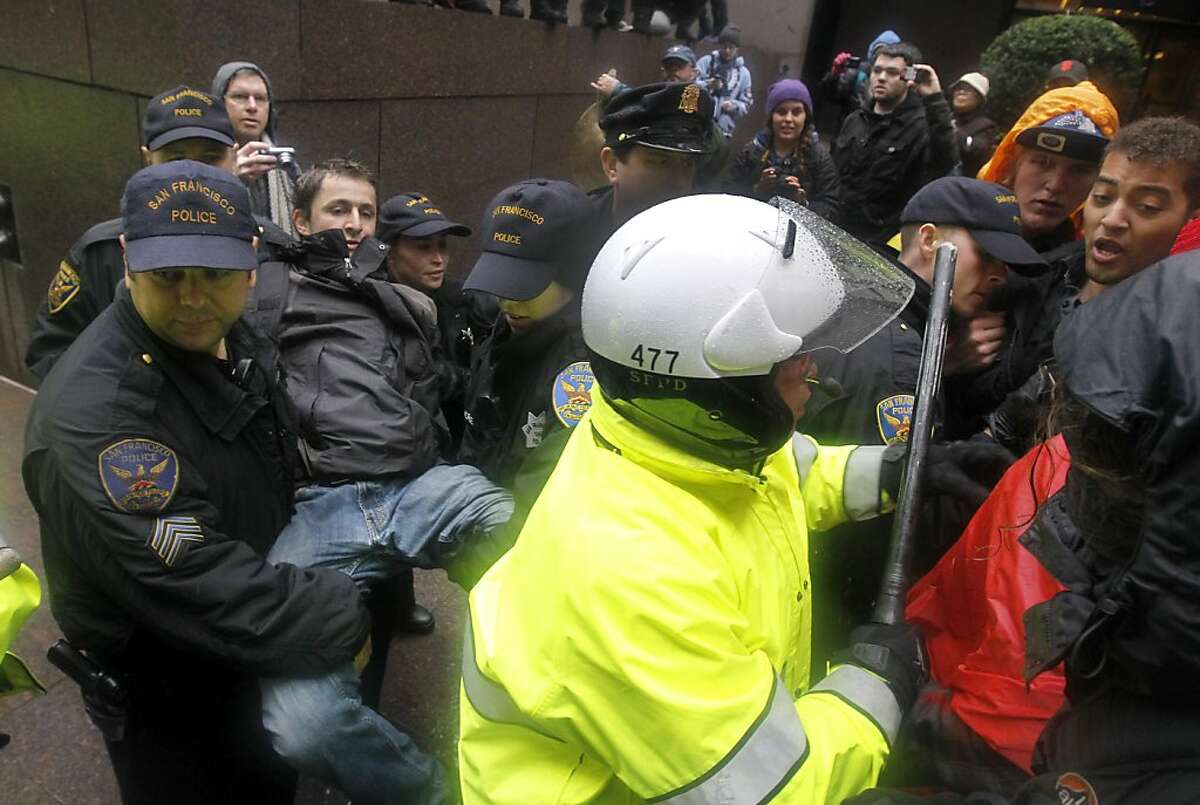 Police officers arrest an Occupy protester for trespassing at 555 California during a day of action against corporations and financial institutions in San Francisco, Calif. on Friday, Jan. 20, 2012.