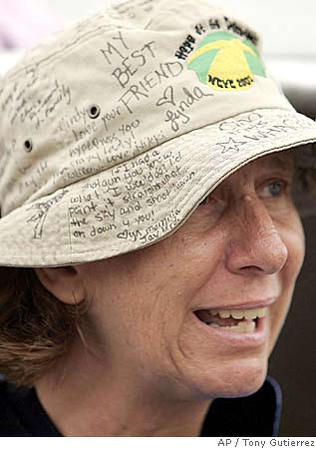 Cindy Sheehan of Vacaville, Calif., wears a hat with messages of support from friends as she chats with a reporter on the country road that leads to President Bush's ranch near Crawford, Texas, Wednesday, Aug. 10. 2005. (AP Photo/Tony Gutierrez)