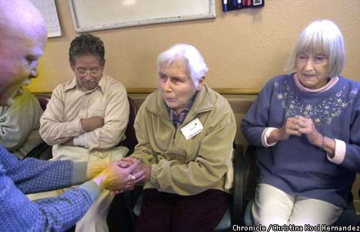 Fred Burns (left) assists Annie in a group exercise as Jesus and Pauline look on at the center, where state cuts could affect services. Christina Koci Hernandez/The Chronicle