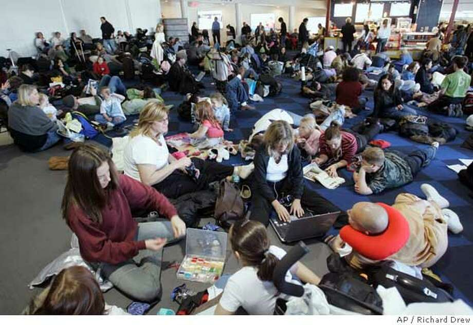 """JetBlue Airways Corp. passengers fill the terminal floor as they wait for flights at New York's Kennedy Airport, Thursday Feb. 15, 2007. JetBlue tried to calm a maelstrom of criticism Thursday, after passengers were left waiting on planes at a New York airport for as long as nine hours during a snow and ice storm. Calling the delays """"unacceptable,"""" the airline said in a statement it would offer refunds and free flights to passengers who were delayed on planes for more than three hours. (AP Photo/Richard Drew) Photo: RICHARD DREW"""