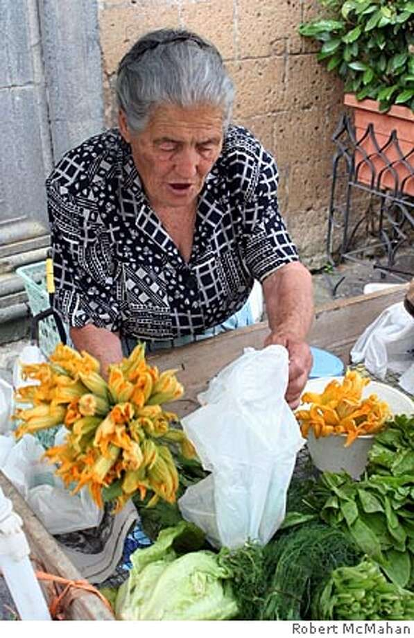 SOUTH10_0548.jpg Lady selling squash blossoms at the farmers' market in Orvieto, Italy. Photo by ROBERT McMAHAN / Freelance Photo: ROBERT McMAHAN