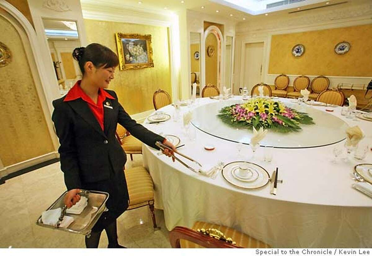Chinese servers set up table at the Tianan Danzi Mian restaurant in Shanghai on 19 September 2006. Photo by Kevin Lee for San Francisco Chronicle