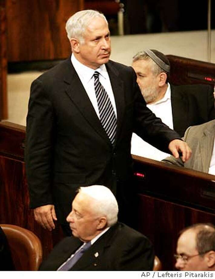 ** FILE ** Israeli Finance Minister Benjamin Netanyahu, top, arrives to the Knesset, Israel's parliament, as Prime Minister Ariel Sharon, bottom, and Foreign Minister Silvan Shalom, bottom right, look on during a vote on the government's proposed Gaza disengagement plan in Jerusalem, in this Tuesday, Oct. 26, 2004 file photo. Finance Ministry officials confirmed Sunday, Aug. 7, 2005 that Benjamin Netanyahu submitted resignation as Israel's finance minister. (AP Photo/Lefteris Pitarakis) Photo: LEFTERIS PITARAKIS