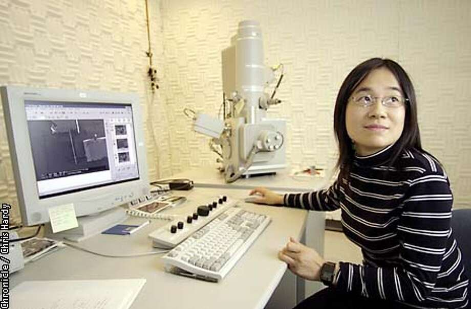 The House of Reps today passed a bill that provides more than $2 billion in federal funding for nanotechnology research Here research scientistJeanie Lau uses a scanning electron microscope to look at two crossed hairs 1/1000th of the diameter of a human hair  5/7/03 in Palo Alto. CHRIS HARDY / The Chronicle Photo: CHRIS HARDY