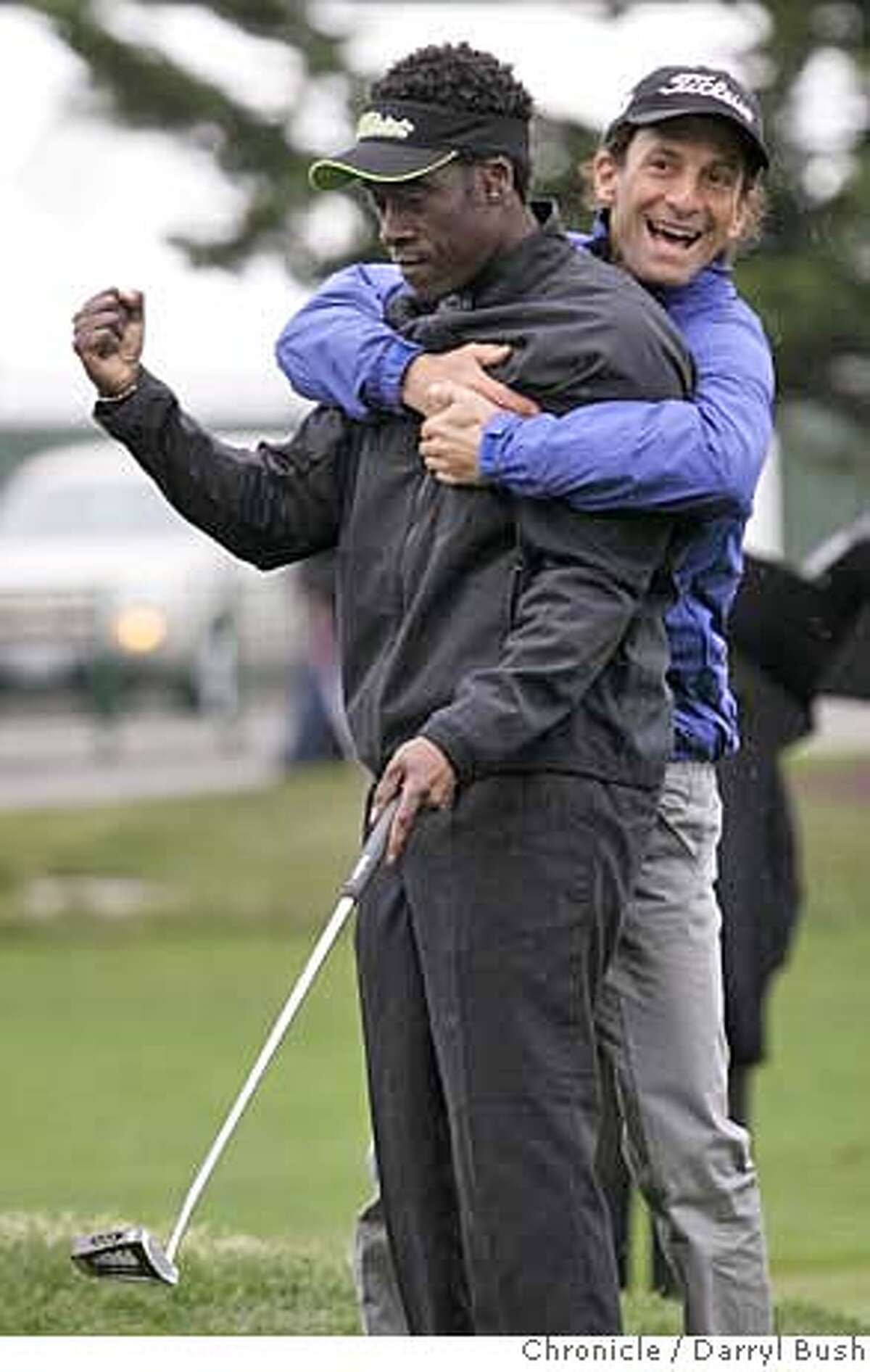 Musician Kenny G, right, hugs actor Don Cheadle who sank a put to win the 2nd hole, during the 2007 3M Celebrity Challenge held Wednesday during practice rounds, at the 2007 AT&T Pebble Beach National Pro-Am at Pebble Beach Golf Links in Pebble Beach, CA, on Wednesday, February, 7, 2007. photo taken: 2/7/07 Darryl Bush / The Chronicle ** (cq)
