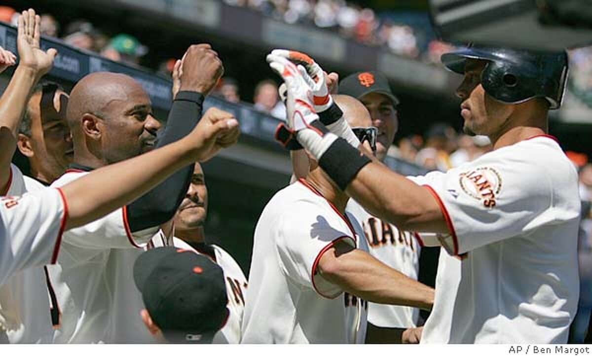 San Francisco Giants' Pedro Feliz, right, is congratulated in the dugout after scoring the go-ahead run against the Colorado Rockies in the eighth inning Thursday, Aug. 4, 2005, in San Francisco. Feliz scored on a double by Lance Niekro. San Francisco won 6-4. (AP Photo/Ben Margot)
