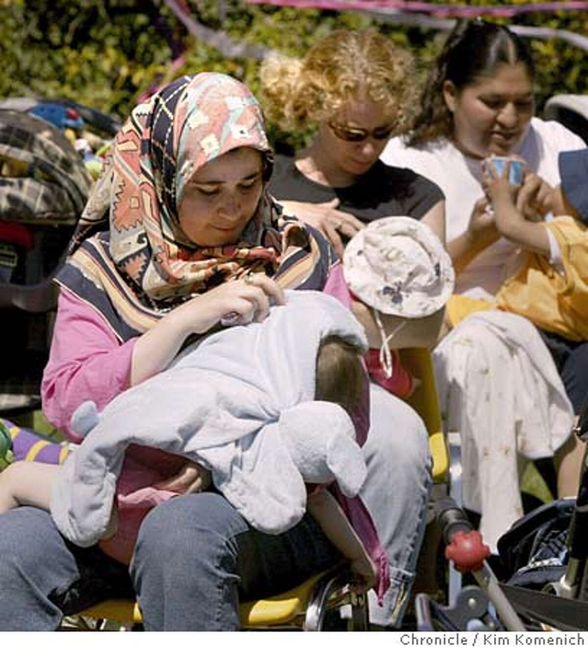 Leila Bouhedda of Berkeley, front, feeds Yasmin, 15 mos., and behjind her, Jeanine Strickland of Berkeley feeds Pepper, 15, weeks, during the event. Woman holding cup in background is not identified. Alameda County's WIC (Women, Infants, Children) Program and the Alameda Breastfeeding Coalition hold a mass breastfeeding in four locations, including Berkeley's Cedar Rose Park, pictured here. San Francisco Chronicle Photo by Kim Komenich 8/4/05