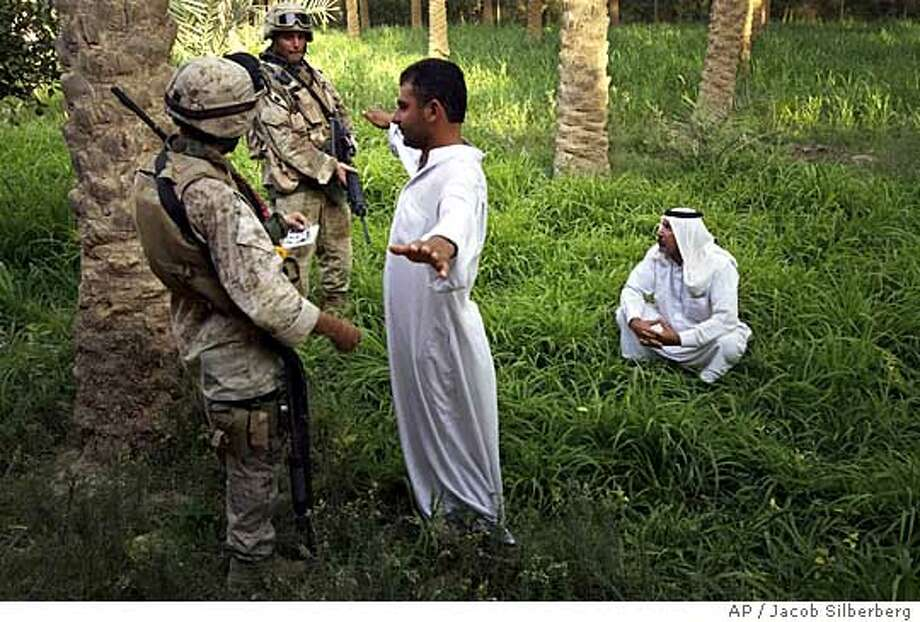 U.S. Marines Sgt. Dennis Osborne, left, of Cincinnati, Ohio and Lance Cpl. Jesse Briggs of Conrad, Montana, from Lima Company of the 3rd Battalion, 25th Regimen from Ohio, question Iraqi men in a palm grove near their house in Parwana, near Haditha, Iraq, Friday, Aug. 5, 2005. A roadside bomb nearby killed 14 Marines and a civilian interpreter, in the deadliest roadside bombing suffered by American forces in the Iraq war. (AP Photo/Jacob Silberberg) Photo: JACOB SILBERBERG