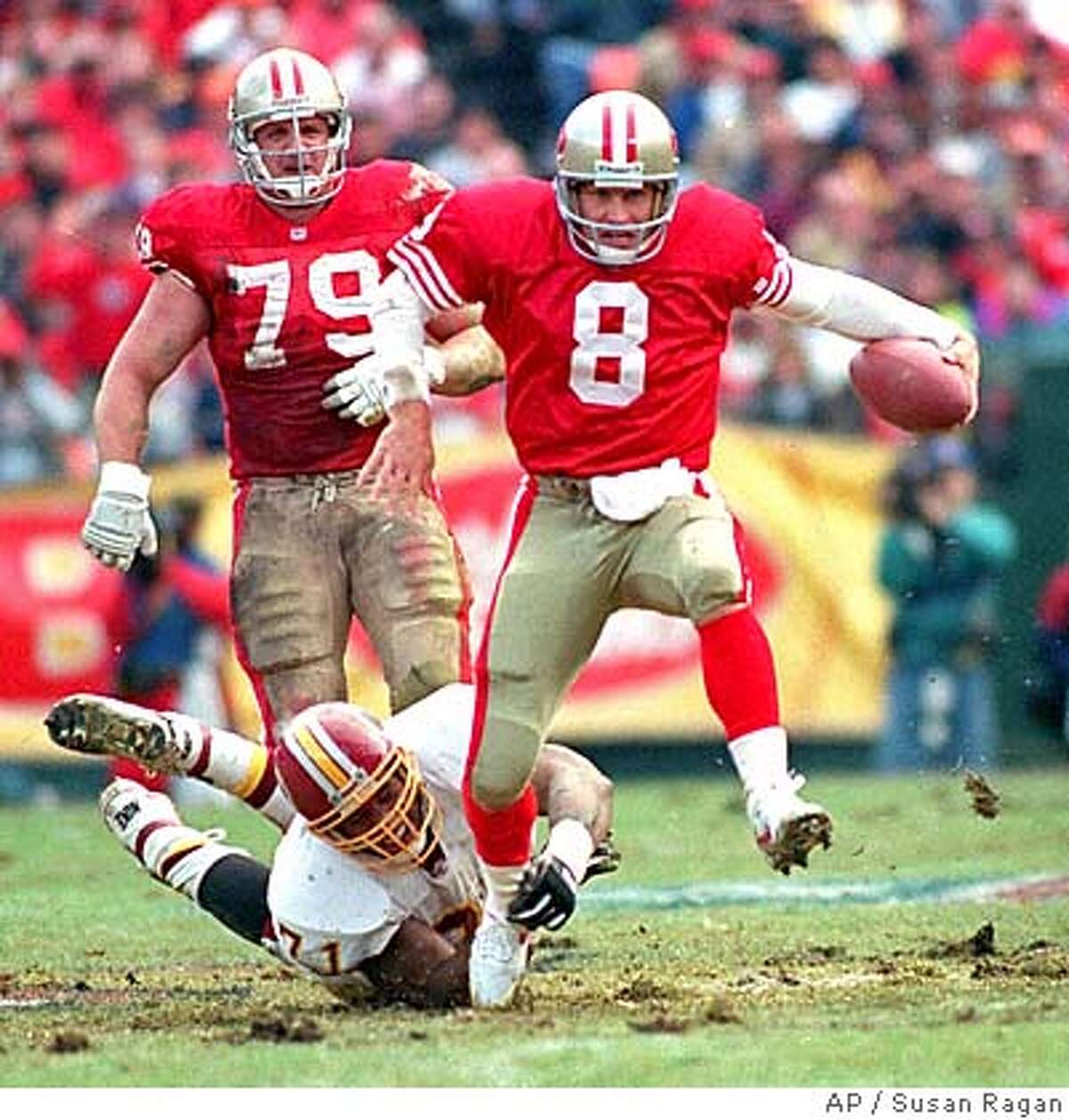 ** FILE ** San Francisco 49ers quarterback Steve Young (8) eludes Washington Redskins' Charles Mann to scramble for a first-half first down during NFC conference semifinal action at a rain-soaked Candlestick Park in San Francisco, in this Jan. 9, 1993 photo. 49ers' Harris Barton (79) is at rear left. (AP Photo/Susan Ragan)