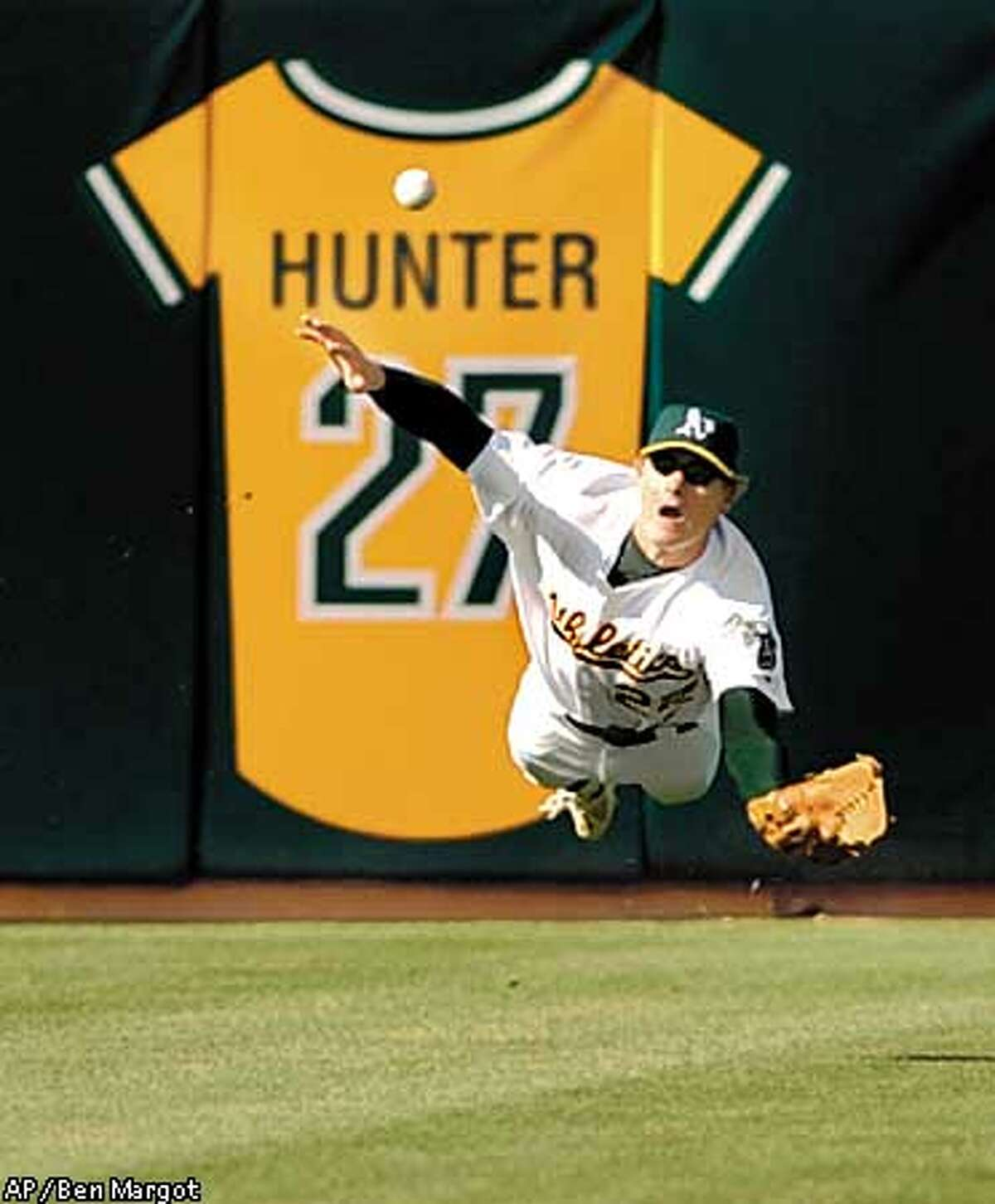 Oakland Athletics center fielder Eric Byrnes dives but can't make the catch on a ball hit by Anaheim Angels' Shawn Wooten, Saturday, April 5, 2003, in Oakland, Calif. Wooten was later tagged out on the same play on his way to second base. The A's won the game, 4-2. (AP Photo/Ben Margot)