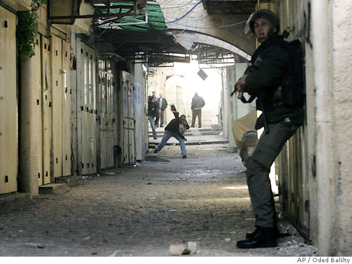 An Israeli police officer, right, calls for reinforcements during clashes with Palestinian stone throwers in the narrow alleyways of east Jerusalem's Old City, Friday, Feb. 9, 2007. Hundreds of angry Muslim worshippers threw stones at police and scuffled with them on Friday in an eruption of outrage over contentious Israeli renovation work at the disputed holy site in Jerusalem's Old City.(AP Photo/Oded Balilty)