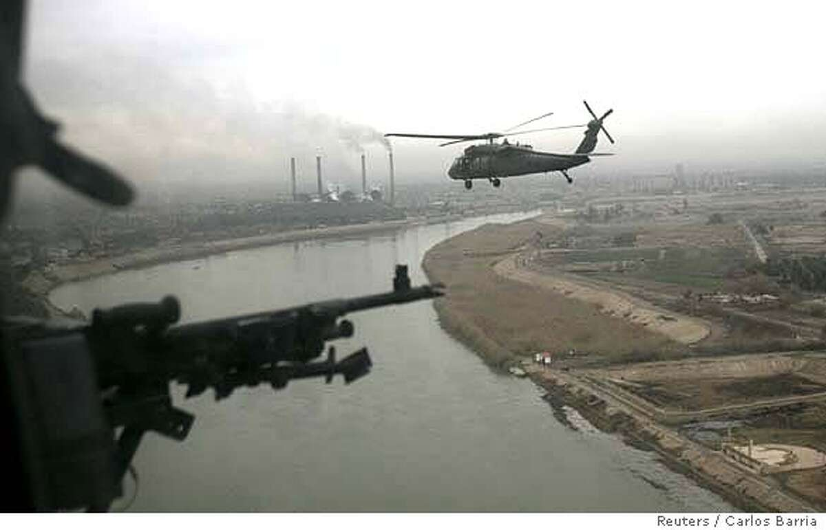 A U.S. Blackhawk helicopter flies over Baghdad February 7, 2007. REUTERS/Carlos Barria (IRAQ)