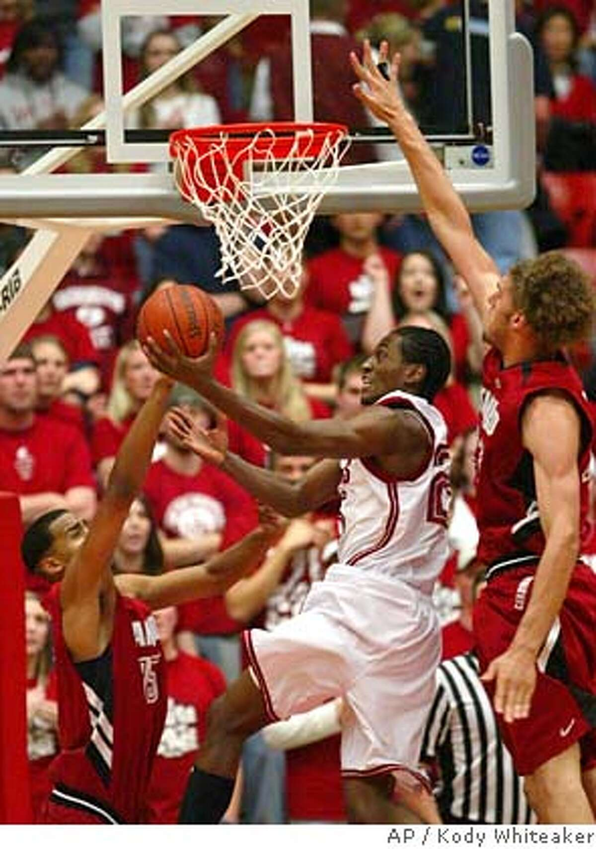 Washington State guard Kyle Weaver, center, attempts a lay-up against Stanford defenders, Robin Lopez, right, and Peter Prowitt in the first half on Thursday, Feb. 8, 2007, in a college basketball game in Pullman, Wash.(AP Photo/Kody Whiteaker)