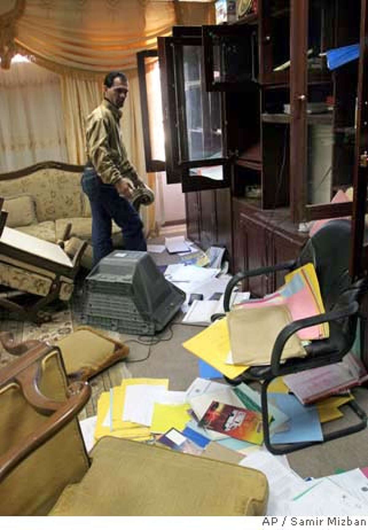 A man stands amid scattered furniture and papers inside the Iraqi Health Ministry offices in Baghdad, Iraq, Thursday, Feb. 8, 2007. Iraqi forces stormed the offices of the Health Ministry on Thursday and detained a senior ministry official accused in alleged corruption and infiltration of the ministry that has funneled millions of dollars to Shiite militiamen blamed for much of the recent sectarian violence in the capital, the U.S. military said. (AP Photo/Samir Mizban)