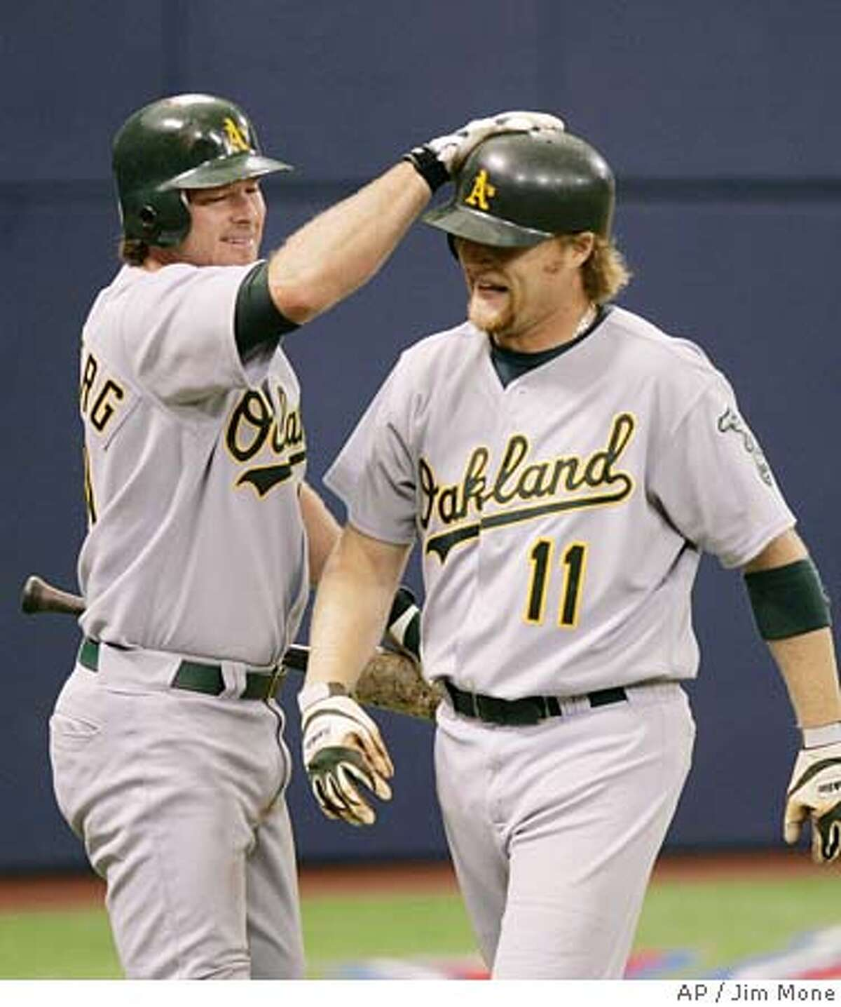 Oakland Athletics' Scott Hatteberg, left, pats Dan Johnson on the helmet after his seventh inning solo home run off Minnesota Twins' Kyle Lohse Thursday, Aug. 4, 2005 in Minneapolis. The Athletics won 5-2, taking three games of the four game series. (AP Photo/Jim Mone)