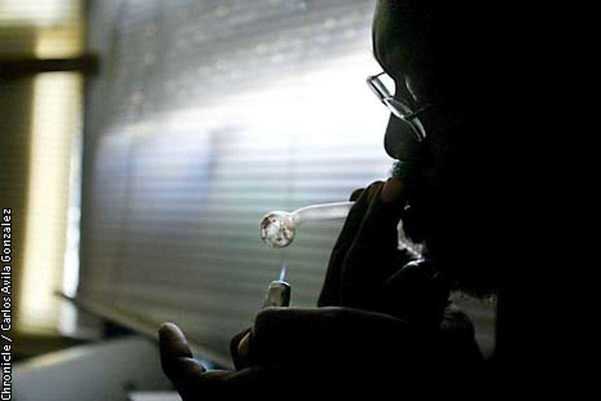 """""""Isaac"""" puts a lighter on the pipe he uses to smoke his crystal methamphetamine as he smokes a small amount in his apartment on Monday, April 21, 2003. (CARLOS AVILA GONZALEZ/SAN FRANCISCO CHRONICLE)"""