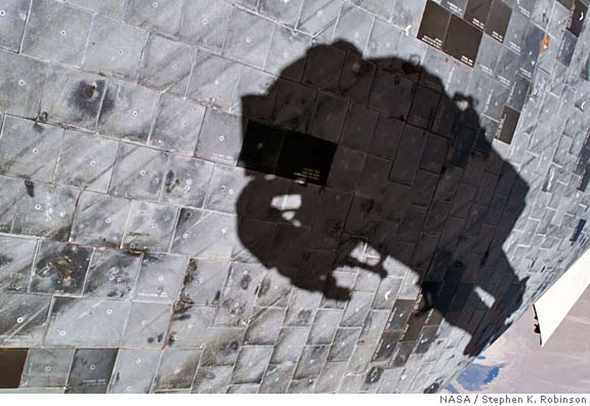 In this photo provided by NASA, a close-up view of a portion of space shuttle Discoverys underside is featured in this image photographed by astronaut Stephen K. Robinson, Discovery mission specialist, during the missions third session of extravehicular activities (EVA), Wednesday Aug. 3, 2005. Robinsons shadow is visible on the thermal protection tiles. (AP Photo/NASA, Stephen K. Robinson) NASA IMAGE TAKEN WEDNESDAY AUG. 3, 2005 MADE AVAILABLE THURSDAY AUG. 4, 2005