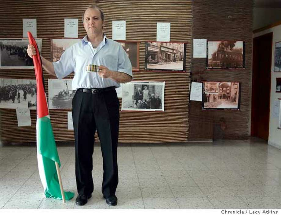 Khaled Kasab Mahameed poses inside his Holocaust museum with a Palestinian flag and a cup of coffee, (coffee is a symbol of hospitality in the Palestinian curture) , June 14, 2005, in Nazareth. Khaled Kasab Mahameed, a Palestinian who has opened a Holocaust museum in Nazareth believing that if the Palestinians understood the Holocaust it would help gain peace in the Mideast , June 14, 2005, in Israel. Photographer Lacy Atkins Photo: LACY ATKINS