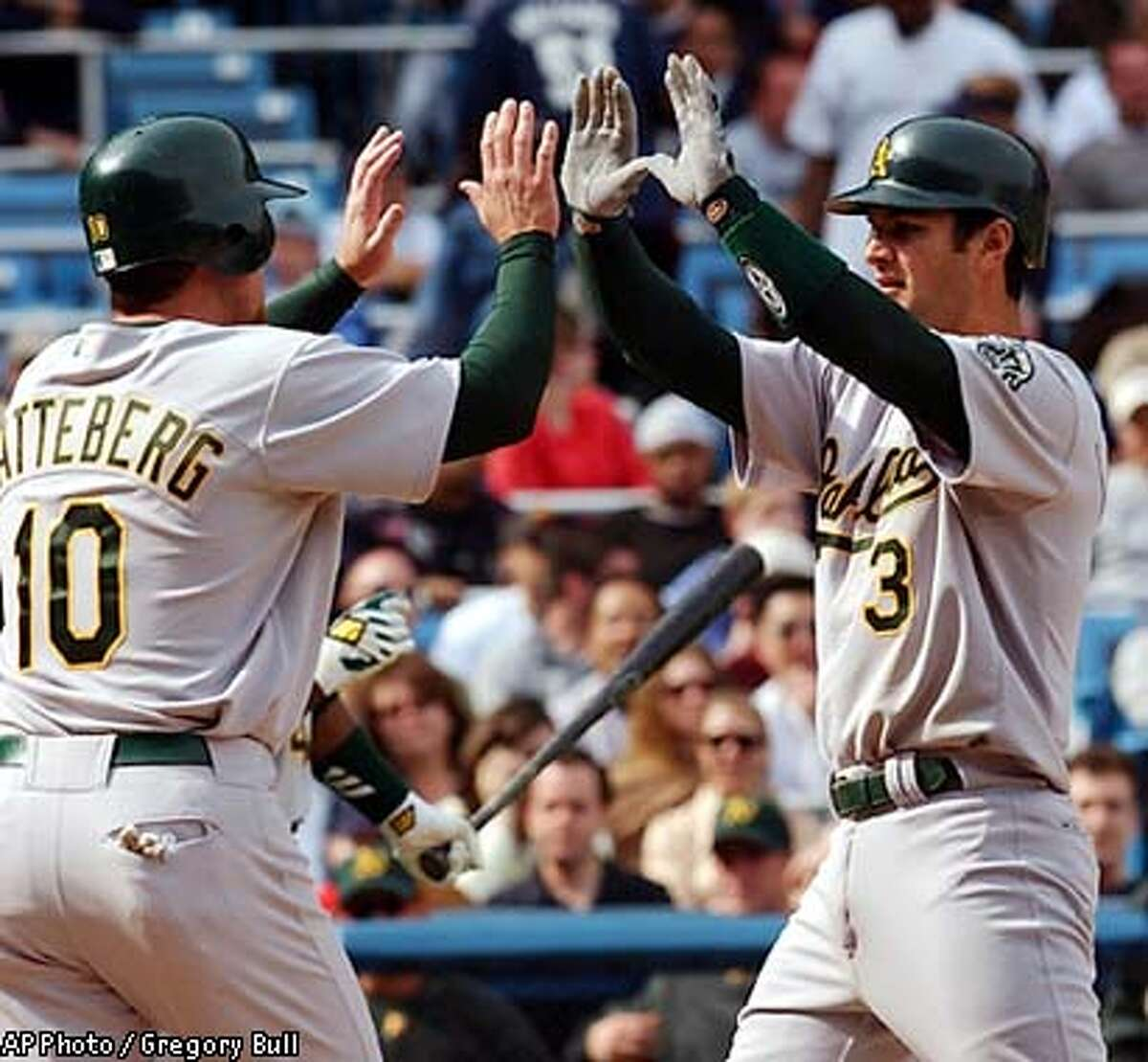 Oakland Athletics' Eric Chavez, right, is congratulated by teammate Scott Hatteberg after his two-run home run in the tenth inning to beat the New York Yankees at Yankee Stadium in New York, Saturday, May 3, 2003. (AP Photo / Gregory Bull)