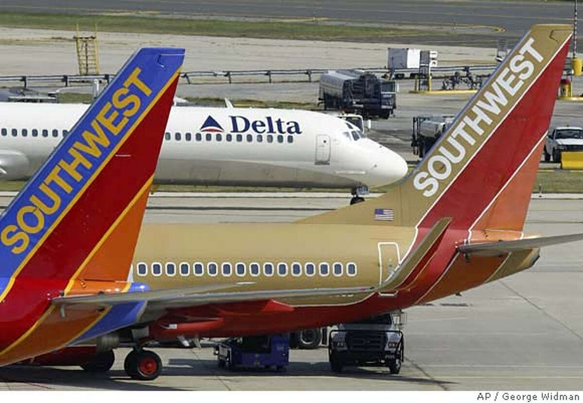 Two Southwest Airlines jets are seen in front of a taxiing Delta jet at Philadelphia International Airport Thursday, Sept. 23, 2004. Low-cost carrier Southwest Airlines Inc. on Thursday, April 14, 2005, said first-quarter earnings nearly tripled, citing higher traffic in March, cost cutting and successful financial management of fuel costs.(AP Photo/George Widman) Ran on: 04-15-2005 Photo caption SEPT. 23, 2004, PHOTO