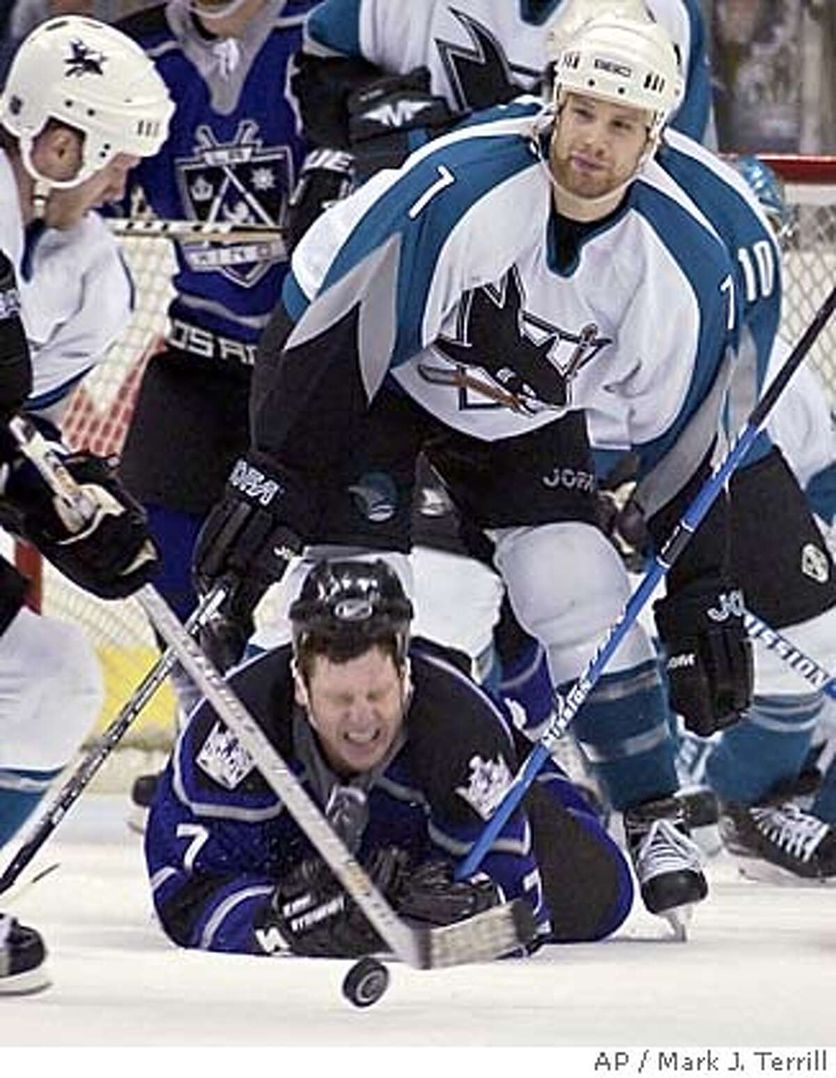Los Angeles Kings' Derek Armstrong of Canada falls to the ice in front of San Jose Sharks' Brad Stuart of Canada as the Sahrk's Nils Ekman of Sweden takes the puck during the third period, Thursday night, March 18, 2004, in Los Angeles. The Sharks won the game 5-3. (AP Photo/Mark J. Terrill)