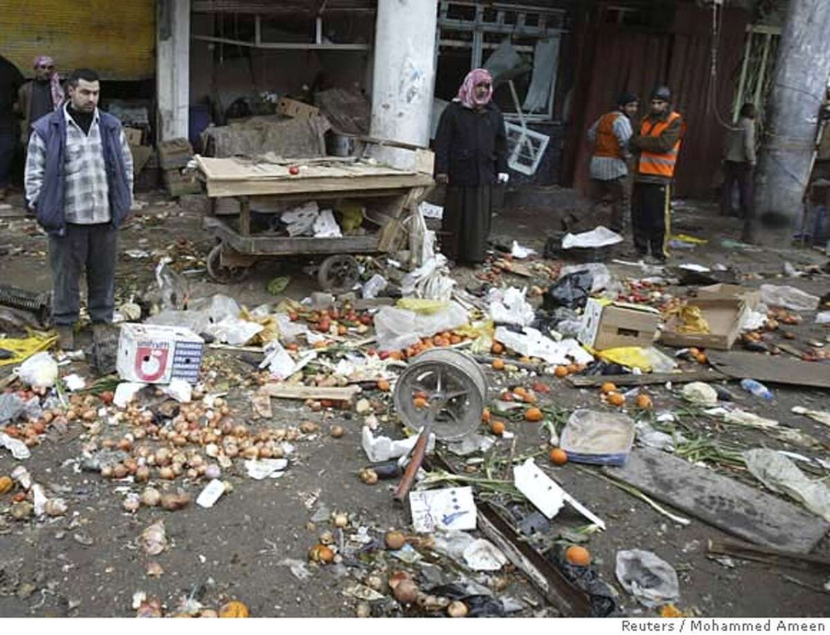 Residents look at scattered fruit and vegetables on the ground the morning after a suicide bomb attack in a market in Baghdad, February 4, 2007. A suicide bomber killed 135 people on Saturday in the deadliest single bombing in Iraq since the 2003 war, driving a truck laden with one tonne of explosives into a market in a mainly Shi'ite area of Baghdad. REUTERS/Mohammed Ameen (IRAQ) 0