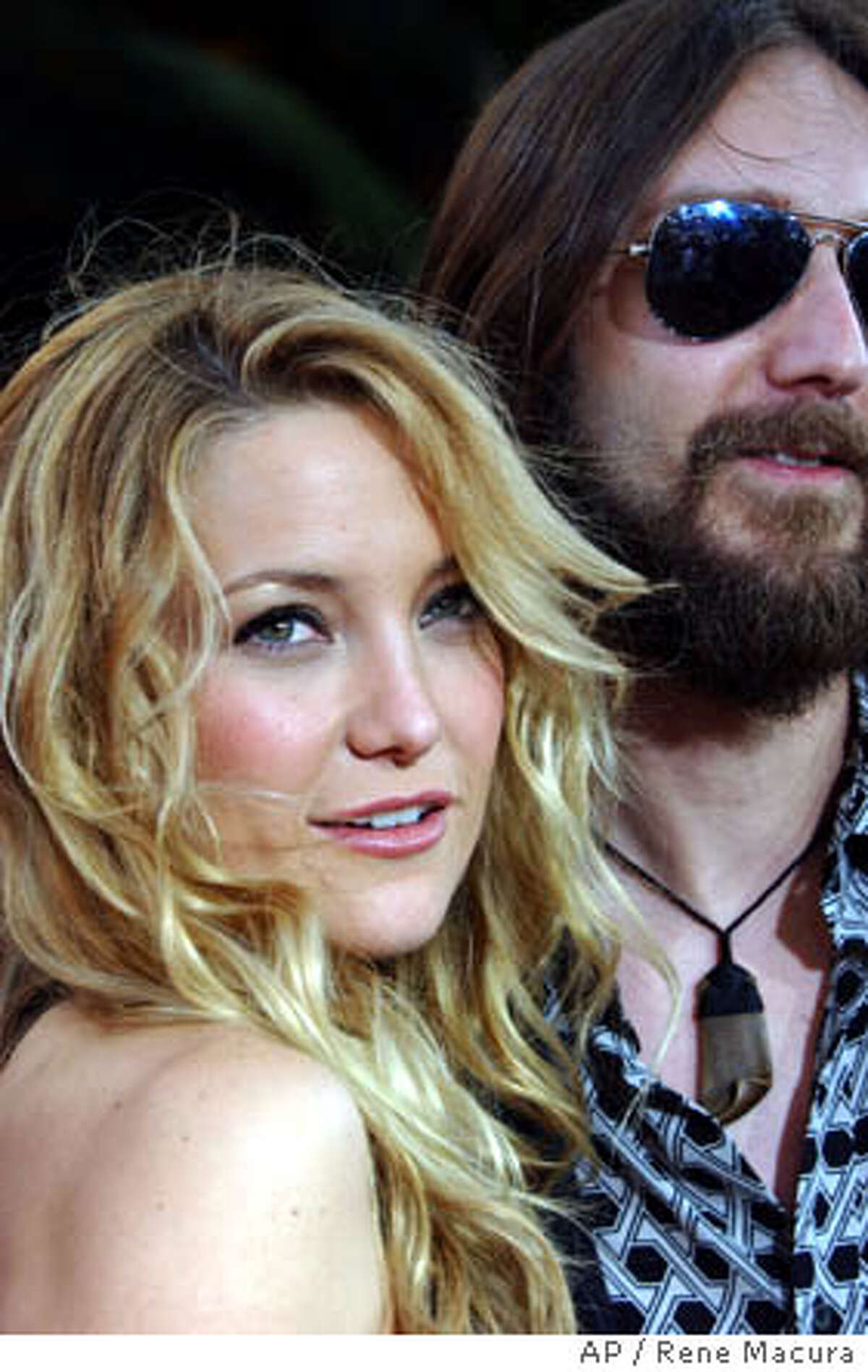 Kate Hudson, left, and her husband Chris Robinson, right, pose for photographers on the red carpet before the premiere of