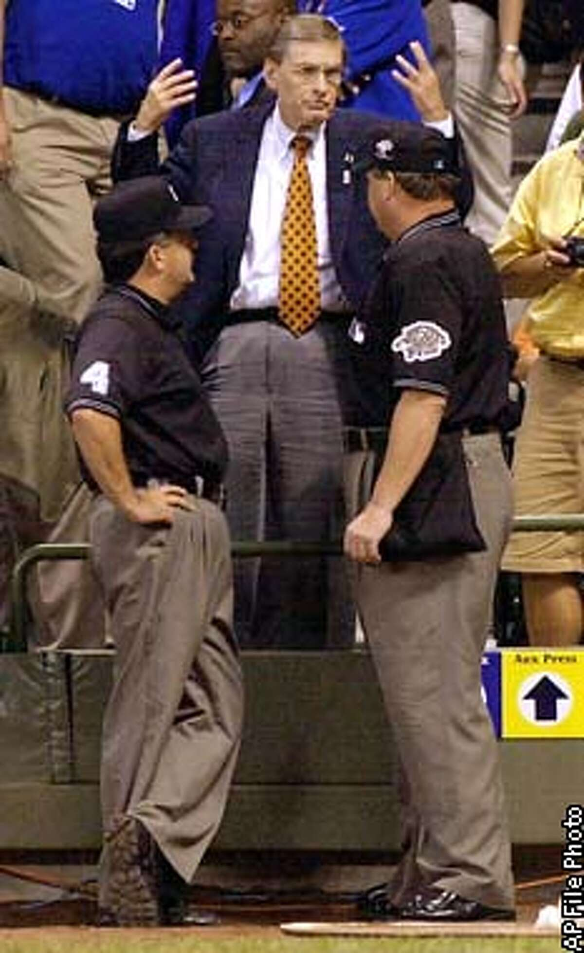 Baseball Commissioner Bud Selig throws up his arms while talking with the umpires in the 11th inning of the in Milwuakee, Tuesday, July 9, 2002. The game was call at the bottom of the inning with the score tied at 7-7. (AP Photo/Charlie Neibergall)