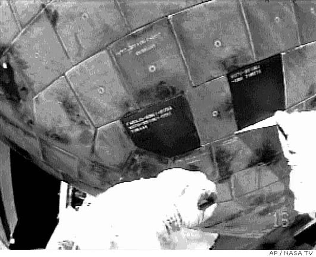 ** FIRST IN A SERIES OF THREE ** A helmet-mounted camera shows astronaut Steve Robinson removing a gap filler on the underside of the Discovery on Wednesday, Aug. 3, 2005. This is the first time in spacewalking history that an astronaut has ventured under the belly of a and performed repairs. (AP Photo/NASA TV)
