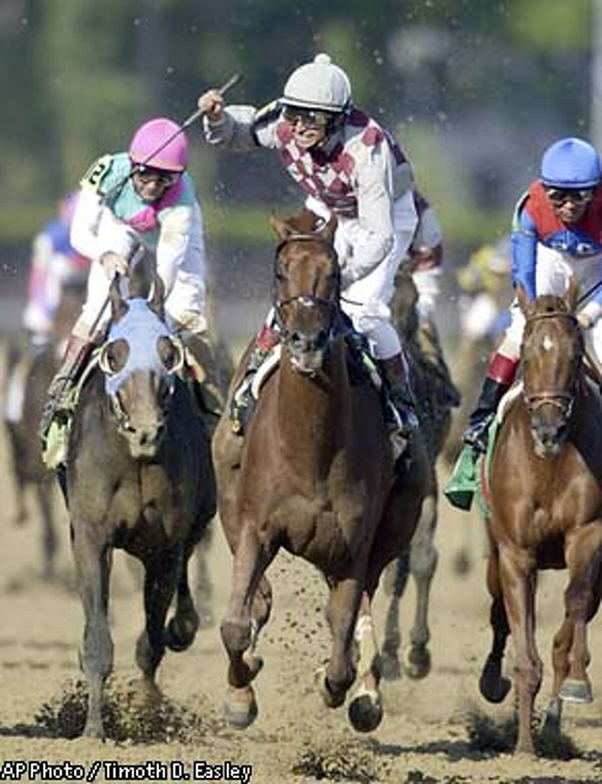 Jockey Jose Santos reacts after riding Funny Cide to victory in the 129th running of the Kentucky Derby on Saturday, May 3, 2003, at Churchill Downs in Louisville, Ky. At left is second place finsher Empire Maker and at right is third place finisher Peace Rules. (AP Photo / Timoth D. Easley)