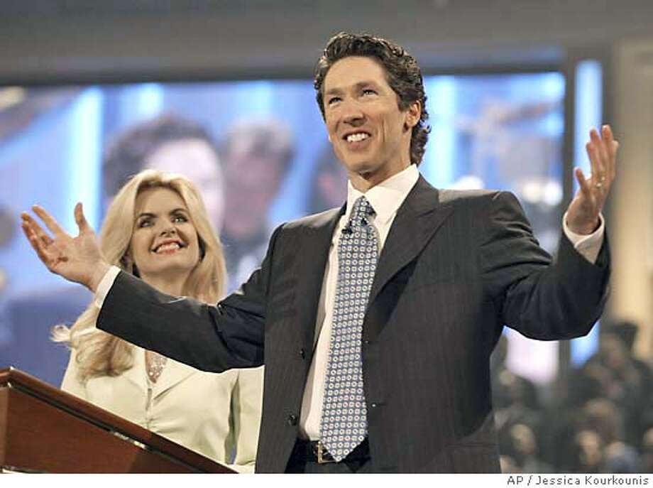 Televangelist and best-selling author, Joel Osteen, right, and his wife, Victoria, left, celebrate the grand opening of the new home for the Lakewood Church, formerly the Compaq Center, Saturday, July 16, 2005, in Houston. The arena that basketball fans once packed to see the NBA's Houston Rockets is taking on a new role, home to the largest congregation in the nation. It took more than 15 months and $75 million to convert the arena into the new home of the largest and fastest growing congregation in the nation. AP Photo by Jessica Kourkounis Photo: JESSICA KOURKOUNIS