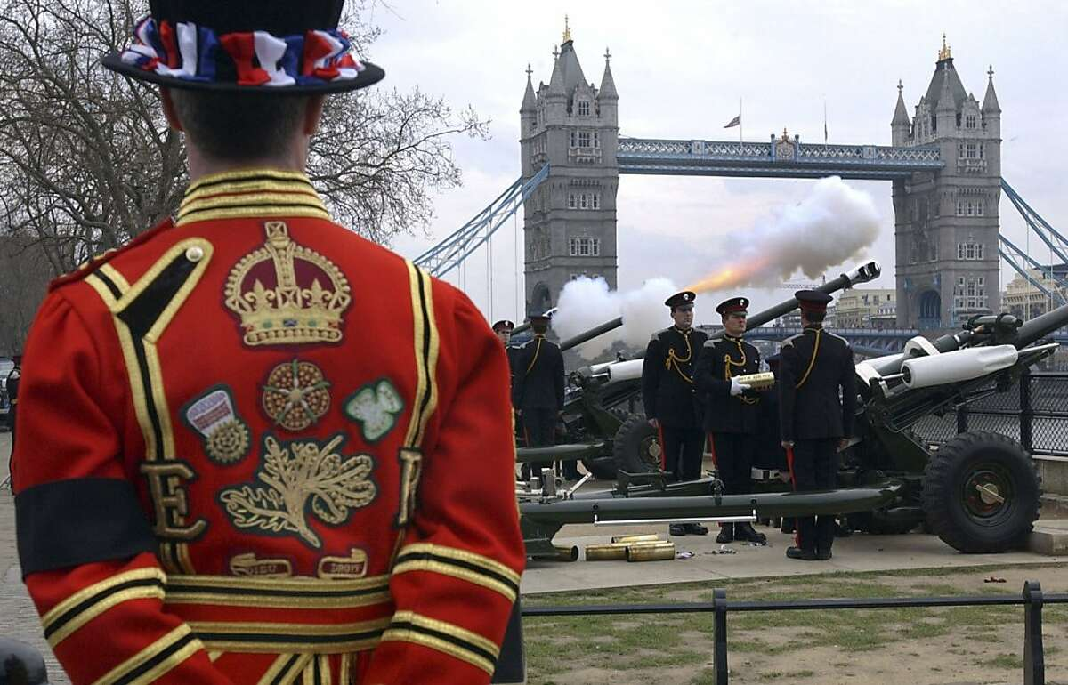 A Beefeater wearing a black armband watches as members of the Honourable Artillery Company fire a 41-gun salute in tribute to Britain's Queen Elizabeth the Queen Mother, at the Tower of London in this April 1, 2002 file photograph.