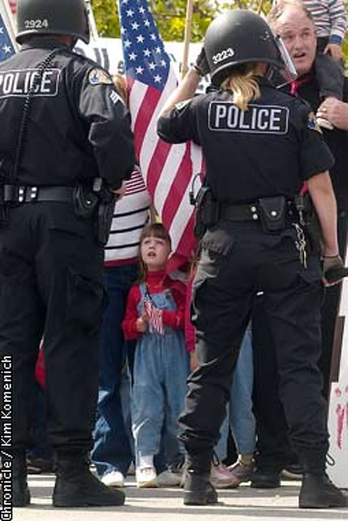 Jillian Hoglan, 3, looks up at police offcers during the protest. Her family was among those supporting Pres. Bush. Police hold the line and keep the peace between protesters and supporters along Coleman Avenue during Pres. George Bush's speech at United Defense in Santa Clara KIM KOMENICH / The Chronicle
