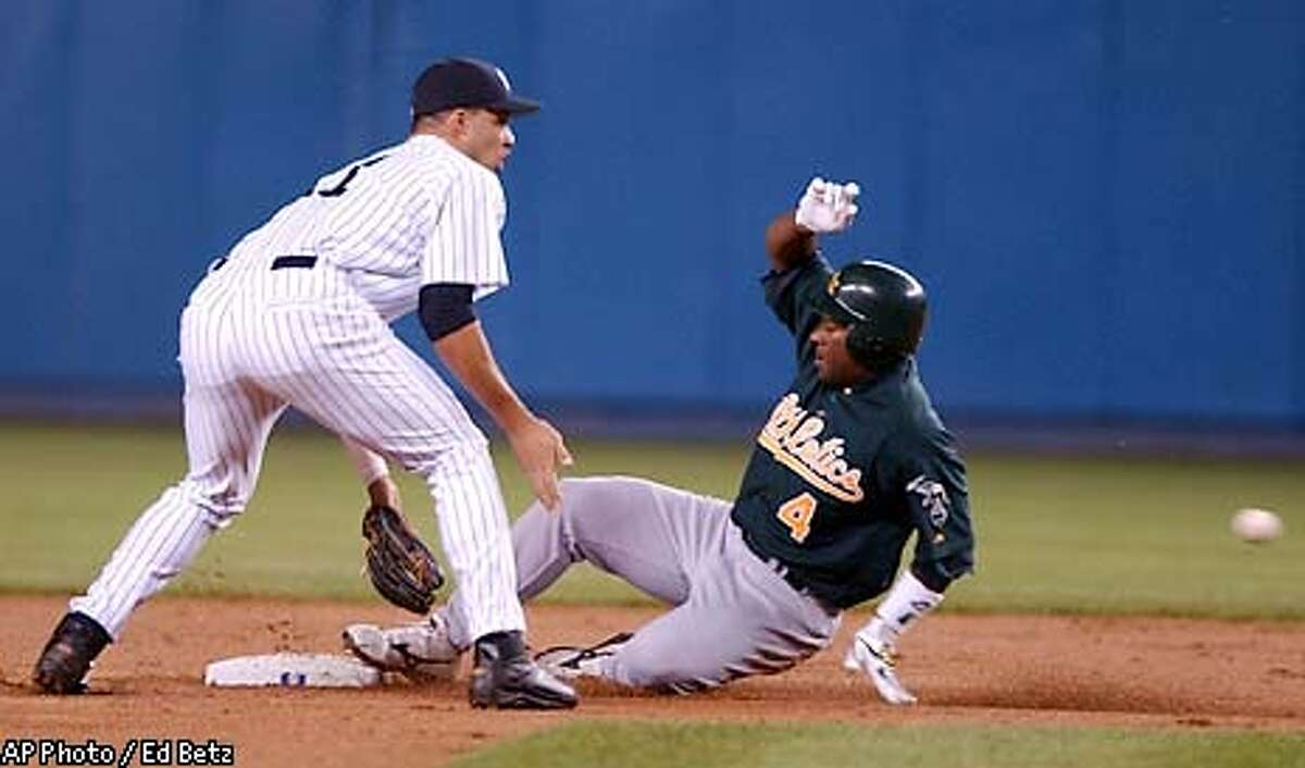 Oakland Athletics' Miguel Tejada slides into second ahead of the ball as New York Yankees shortstop Erick Almonte waits for the ball during the first inning, Friday, May 2, 2003, at Yankee Stadium in New York. (AP Photo/Ed Betz)