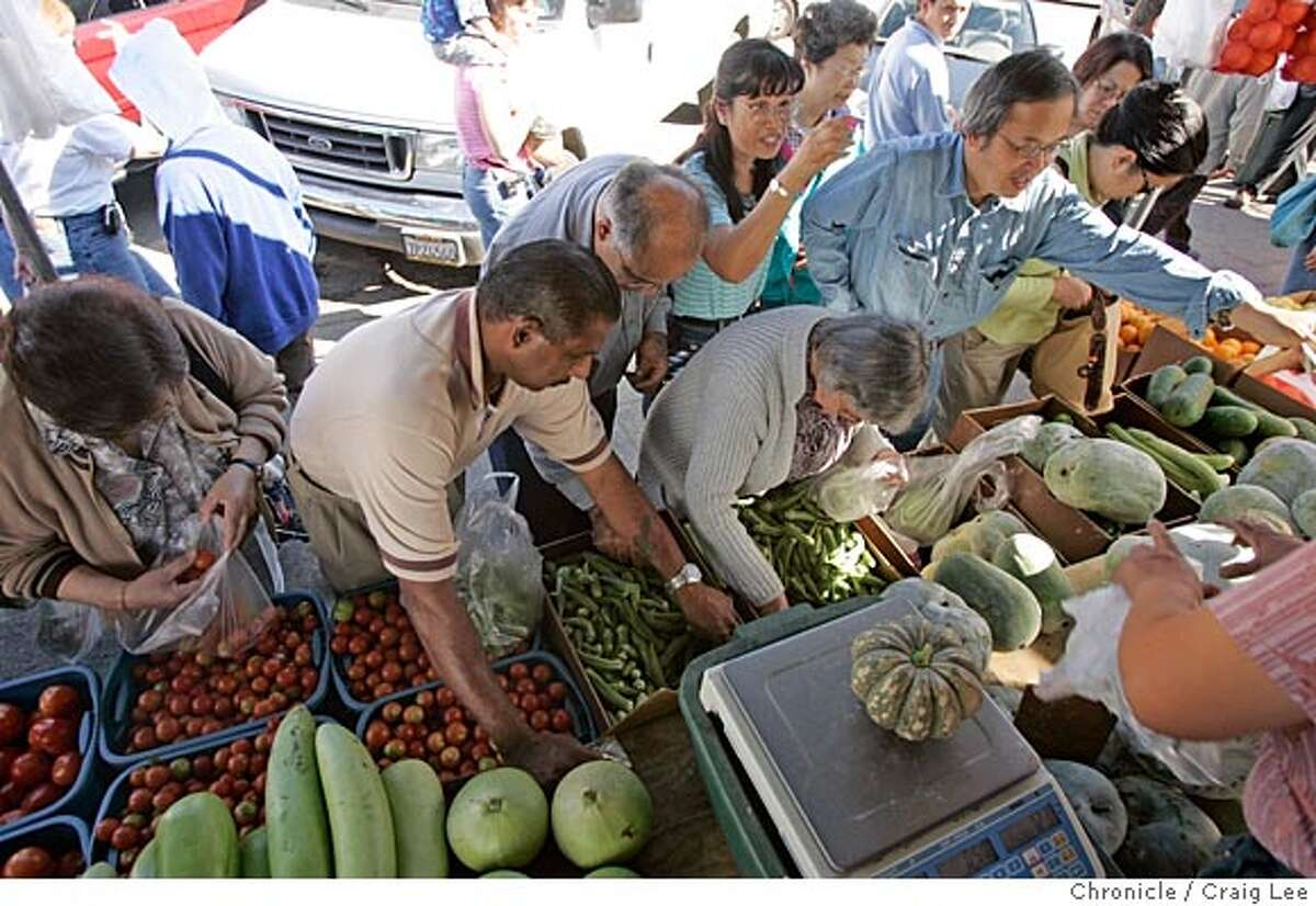 Photo of the people buying their produce. The Xiong family, Hmong tribal people from Laos. This family is from Fresno and drive to San Francisco every Saturday to sell their produce at the Alemany farmers market. Event on 7/23/05 in San Francisco. Craig Lee / The Chronicle