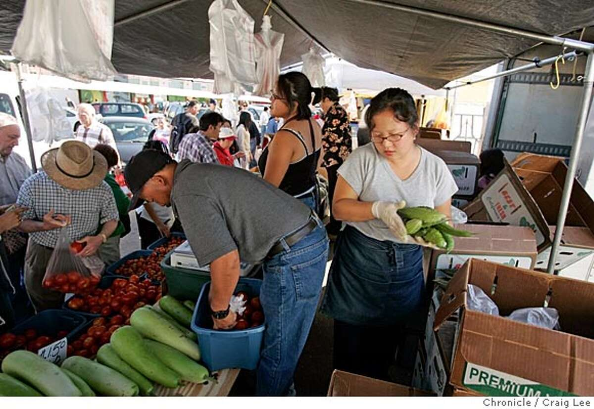 Photo of Zong Yang (right), 27, moving behind her father, Chertai Xiong, at the produce stand. The Xiong family, Hmong tribal people from Laos. This family is from Fresno and drive to San Francisco every Saturday to sell their produce at the Alemany farmers market. Event on 7/23/05 in San Francisco. Craig Lee / The Chronicle