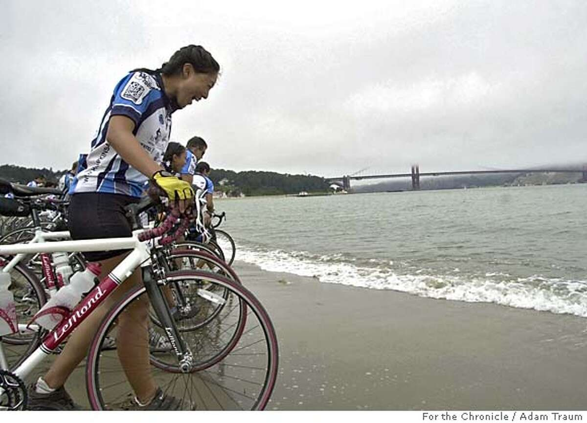 Jessica Lee, right, and 25 other Cyclists from Johns Hopkins dip thier bicycle's front tires into the San Francisco Bay to end their journey. The team raised money, riding cross country 4000 miles with a fundraising goal of $60,000. Each cyclist had to raise $3000 and the team also raised money along the way. Adam Traum/The San Francisco Chronicle