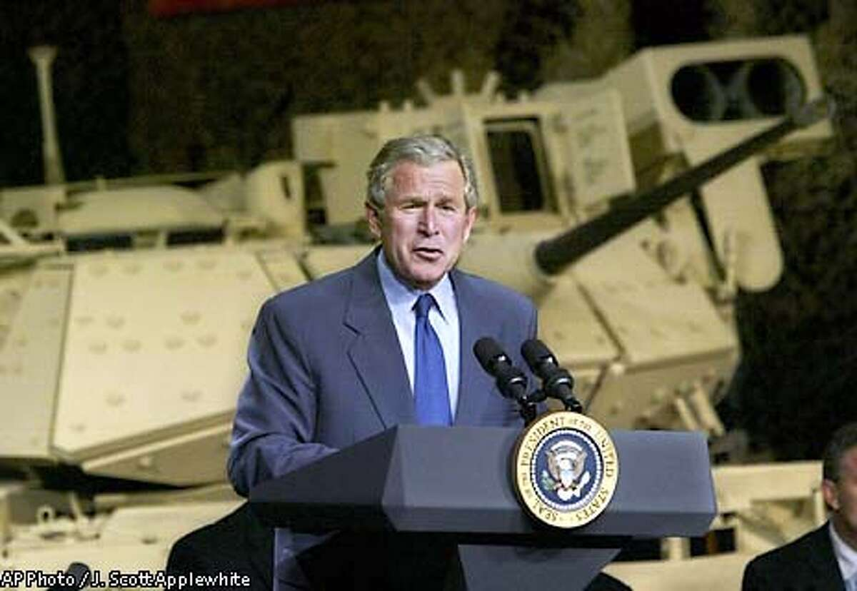 President Bush speaks at United Defense, manufacturer of the Bradley Fighting Vehicle seen at rear, in Santa Clara, Calif., Friday, May 2, 2003. Bush is promoting his economic agenda in Silicon Valley, home of many government defense contractors. (AP Photo/J. Scott Applewhite)