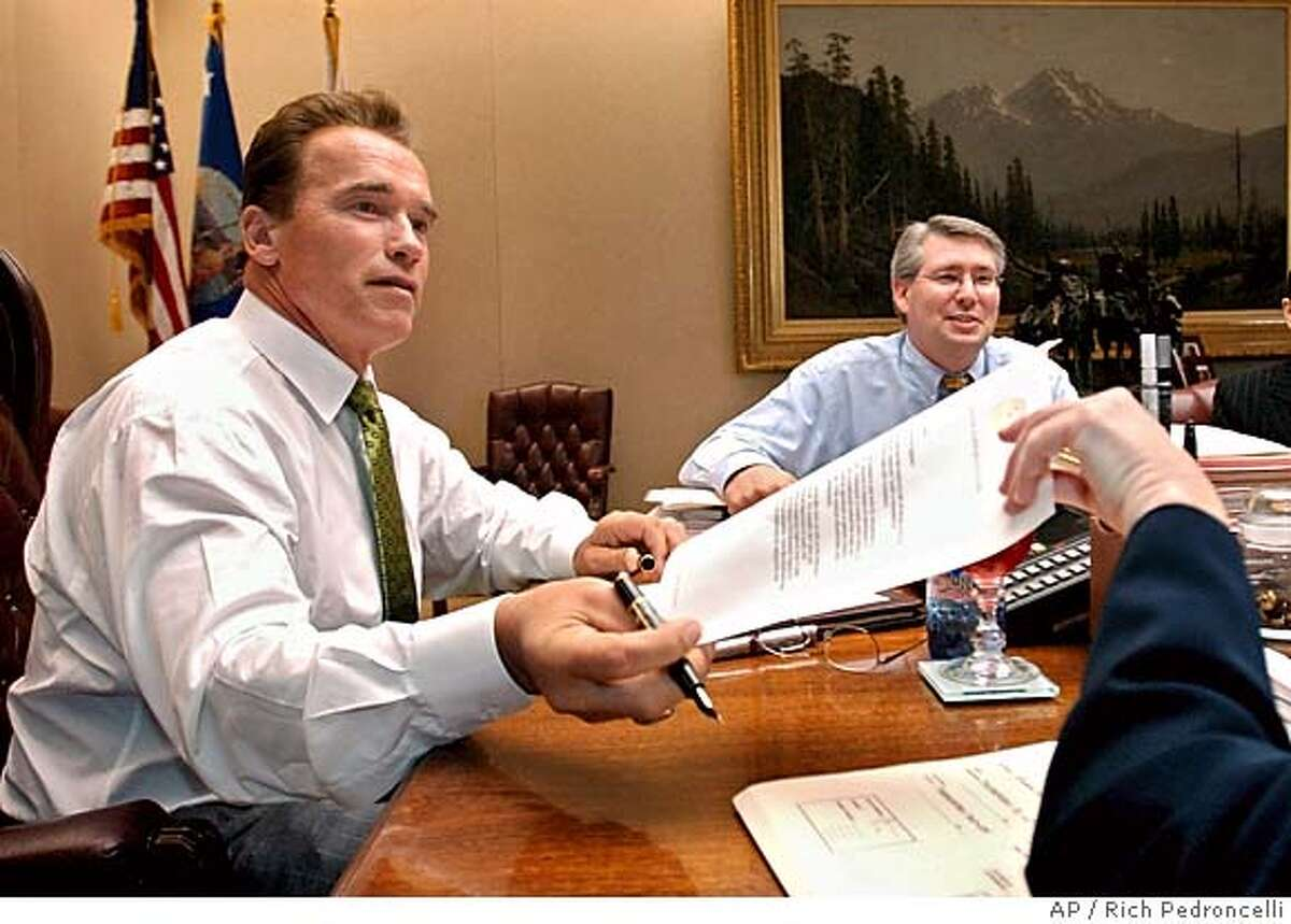 Gov. Arnold Schwarzenegger is handed a veto message by Cynthia Bryant, his deputy legislative secretary, as he plows through the more than 200 pieces of legislation he must act on by the Sept. 30 deadline at the Capitol in Sacramento, Calif., Wednesday, Sept. 29, 2004. Schwarzengger has spent the past month reviewing more than 800 bills passed by the legislature during the end of the legislative session in August. The governor has until midnight Thursday, to either approve or veto the remaining bills. In the background at right is Legislative Secretary Richard Costigan. (AP Photo/Rich Pedroncelli) Ran on: 09-30-2004 Governor Arnold Schwarze- negger vetoed a bill to legalize ownership of ferrets. Ran on: 09-30-2004 Governor Arnold Schwarze- negger vetoed a bill to legalize ownership of ferrets. Ran on: 10-02-2004 Schwarzenegger Ran on: 10-02-2004 Schwarzenegger Metro#MainNews#Chronicle#10/2/2004#ALL#5star##0422383322