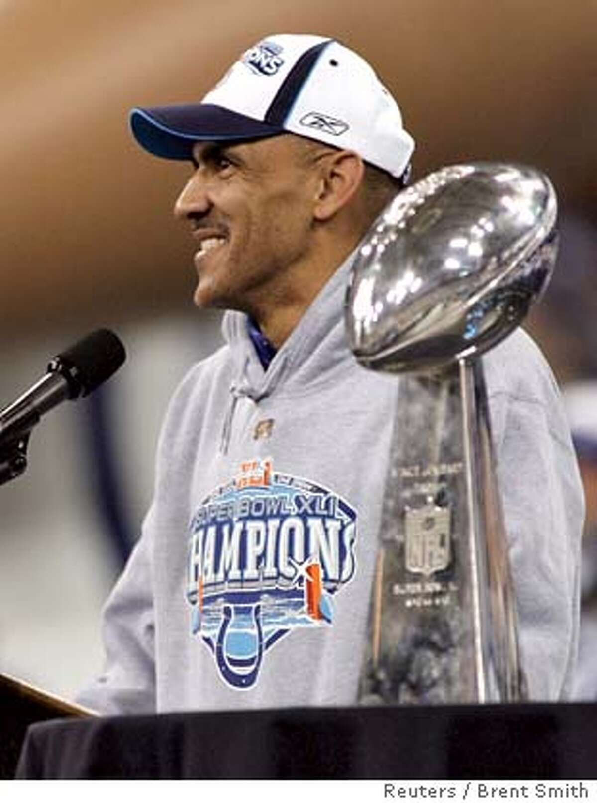 Indianapolis Colts head coach Tony Dungy smiles while standing near the Vince Lombardi Trophy during a rally honoring the Colts' NFL Super Bowl XLI win in Indianapolis February 5, 2007. REUTERS/Brent Smith (UNITED STATES) 0