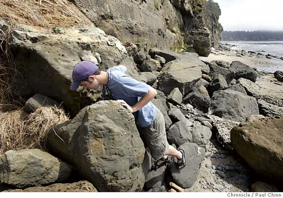 fossils_059_pc.jpg  Paleontology student Bobby Boessenecker looks for signs of prehistoric life in the rocks on the beach on 7/14/05 in Capitola, Calif. Boessenecker is among a loose group of amateur fossil hunters who routinely scour the coastal areas for teeth, bones and shells of ancient ocean creatures.  PAUL CHINN/The Chronicle Due to privacy concerns, only the first names of the children are allowed to be published. Photo: PAUL CHINN