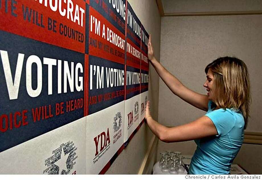 """DEMSXX_001_ CAG.JPG  Jane Fleming, executive director of the Young Democrats of America, posts some of the group's posters in the strategy room at the Holiday Inn in San Francisco, Ca., on Thursday, July 28, 2005. The Young Dems are holding their national convention in San Francisco next week and are vowing to change the image of the five-decade-old organization from a """"social club"""" consisting of a bunch of dorks in blue blazers into a more activist organization. Photo by Carlos Avila Gonzalez / The San Francisco Chronicle  Photo taken on 7/28/05, in San Francisco,CA. Photo: Carlos Avila Gonzalez"""
