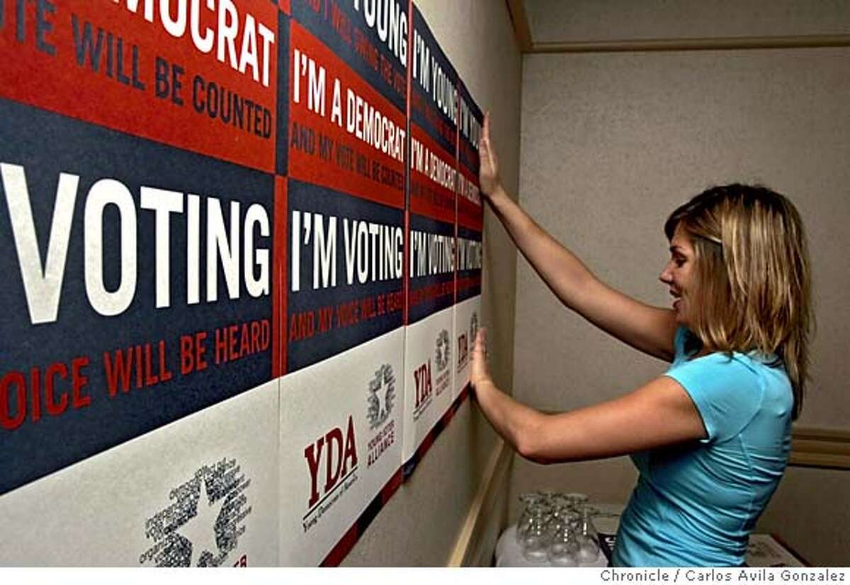 """DEMSXX_001_ CAG.JPG Jane Fleming, executive director of the Young Democrats of America, posts some of the group's posters in the strategy room at the Holiday Inn in San Francisco, Ca., on Thursday, July 28, 2005. The Young Dems are holding their national convention in San Francisco next week and are vowing to change the image of the five-decade-old organization from a """"social club"""" consisting of a bunch of dorks in blue blazers into a more activist organization. Photo by Carlos Avila Gonzalez / The San Francisco Chronicle Photo taken on 7/28/05, in San Francisco,CA."""