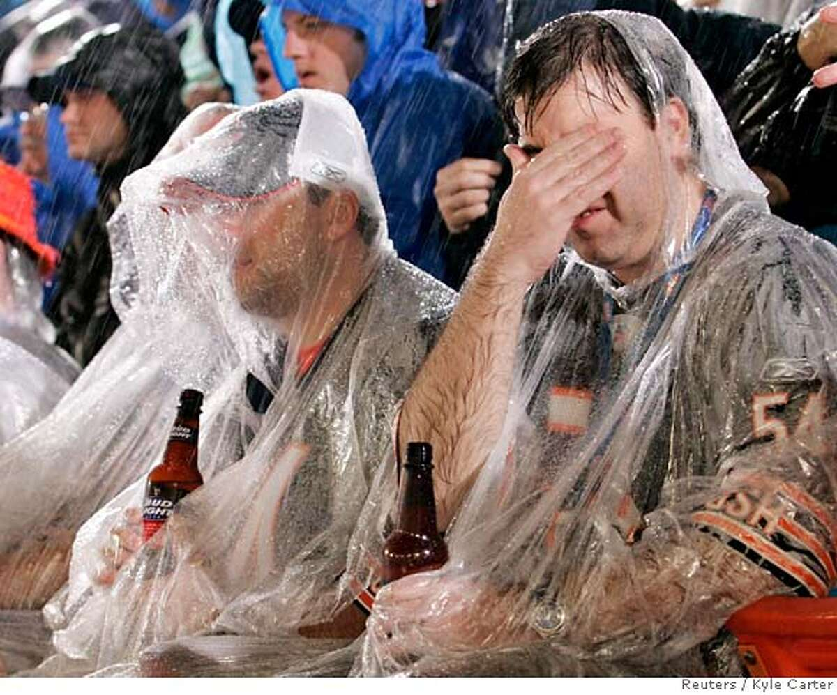 Chicago Bears fan Bill Lynn (R) covers his face in the rain during the NFL's Super Bowl XLI football game between the Bears and the Indianapolis Colts in Miami, Florida February 4, 2007. REUTERS/Kyle Carter (UNITED STATES)