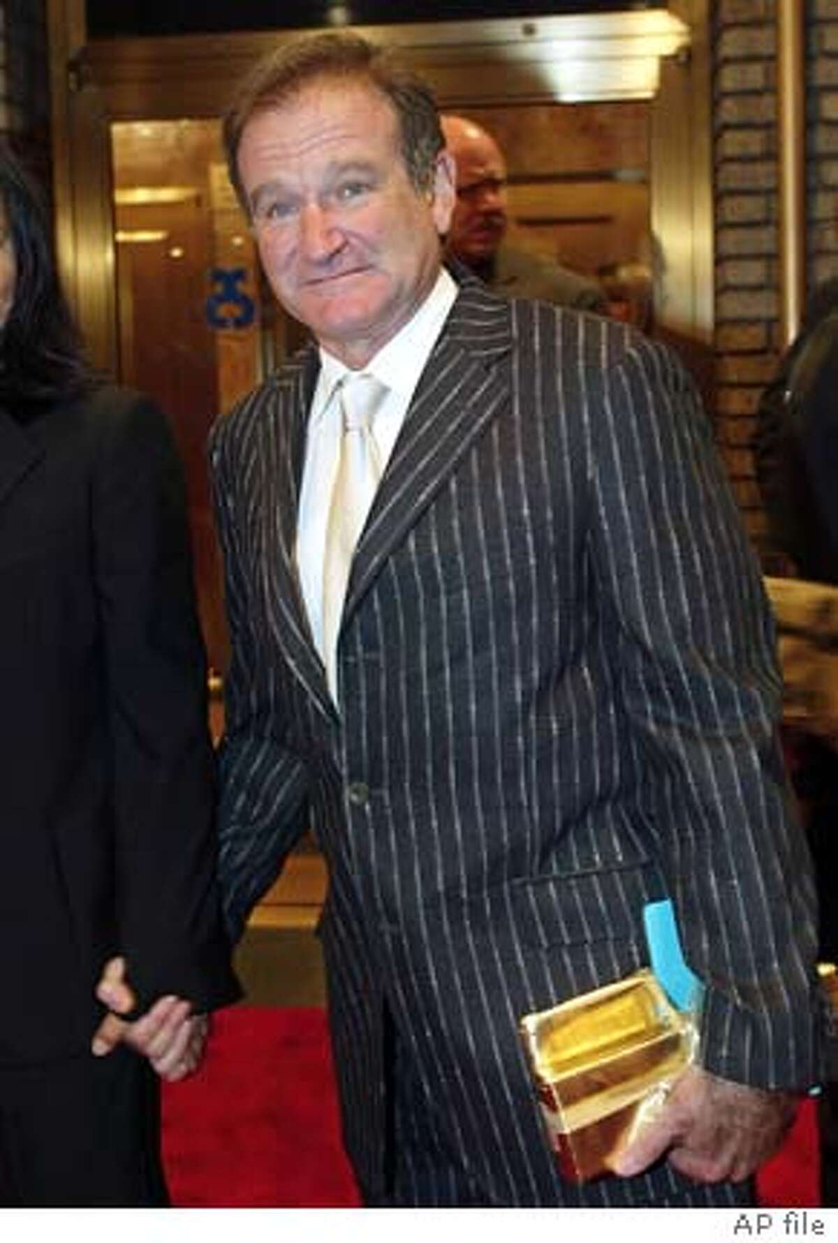 ** FILE ** Actor and comedian Robin Williams arrives at the Broadhurst Theater in Times Square for the opening of Billy Crystal's new show titled 700 Sundays, New York, in this, Dec. 5, 2004, file photo. Williams and his wife, Marsha, offered to donate $80,000 to fix a retaining wall and median strip near their home in San Francisco's Seacliff neighborhood. City supervisor Gerardo Sandoval balked, fearing Williams would be getting preferential treatment. But after city staff assured him that Williams' generosity would free up funds for poorer neighborhoods, Sandoval joined nine colleagues in voting unanimously on Tuesday, July 26, 2005, to accept the comedian's gift. (AP Photo/Stuart Ramson, file)