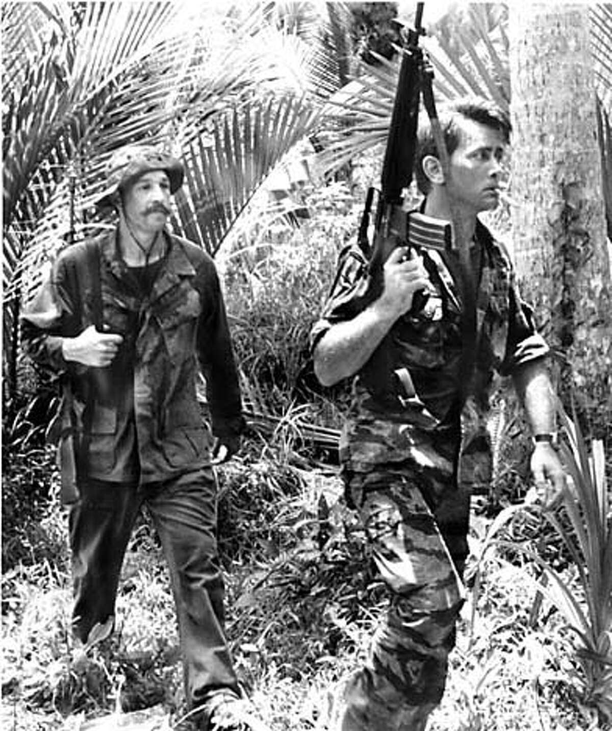Capt. Willard (Martin Sheen), right, and Chef (Frederic Forrest) move cautiously through the Vietnamese jungle, in search of fresh fruit for their dinner in