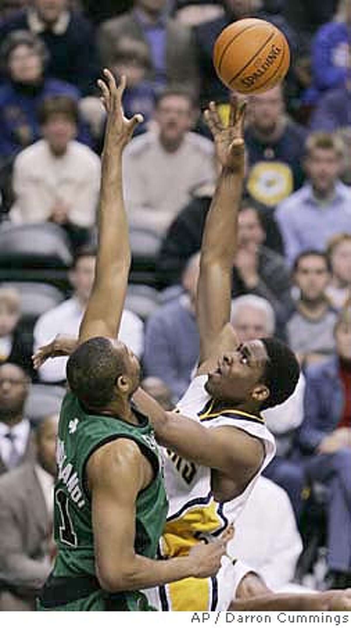 Indiana Pacers forward Ike Diogu, right, puts up a shot over Boston Celtics center Michael Olowokandi, of Nigeria, during the second quarter of an NBA basketball game in Indianapolis, Tuesday, Jan. 30, 2007. (AP Photo/Darron Cummings)