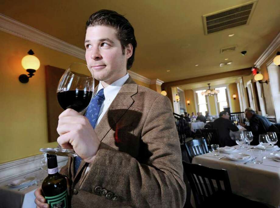 "Chase Hochstin of Greenwich, sommelier for Tarry Lodge, ""noses"" a red wine in the Port Chester, N.Y., restaurant, Friday, Jan. 20, 2012. Photo: Bob Luckey / Greenwich Time"